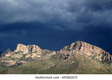 Impending storm with huge dark gray billowing monsoon clouds over the Pusch Ridge mountains in the Tucson Arizona desert