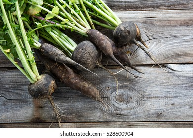 imperfect organic round and long black radishes with fresh green tops and roots on old wood background for authentic agriculture, flat lay