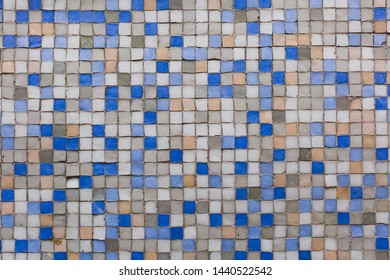Imperfect wall of mosaic tiles blue and neutral colors, old and worn.