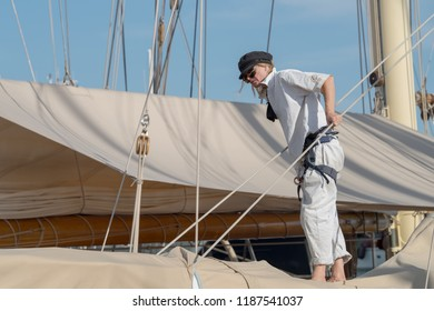 Imperia, Italy - September 9, 2018: Crew member in action on sailboat moored in the harbour of Imperia during stage of the Classic Yachts Challenge