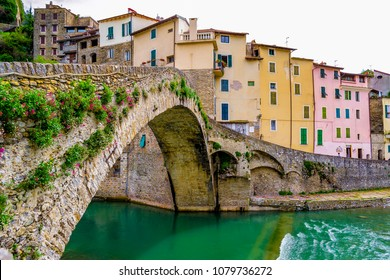IMPERIA, LIGURIA, ITALY - April 14, 2018 : View of the Romanesque bridge, the Nervia creek and the houses of the old village of Dolceacqua.