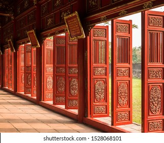 Imperial City of Hue/Vietnam - 03/22/2019: Decorated red doors of corridor at Imperial City of Hue, Vietnam, oblique view