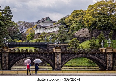 At the Imperial Palace. Two young ladies with umbrellas admire the striking Imperial Palace in Tokyo, Japan. Photograph shot on April 11, 2015