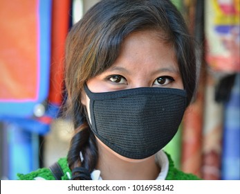 IMPHAL, MANIPUR/INDIA - NOV 10, 2017: Young Indian Manipuri girl with beautiful eyes protects herself against air pollution with a black mouth face mask in downtown Imphal, on Nov 10, 2017.