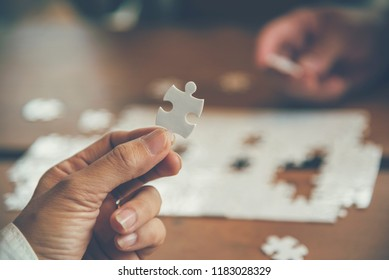 implementation communication strategy improving connections team solution organization.Piece of jigsaw assembly by Implement puzzle. Hands of connect business people group solutions success strategy