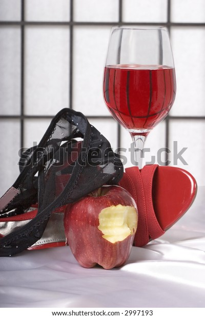 Implied sex with a bite taken from the forbidden fruit.  Black panties with a white bow, red  high heel shoes, wine, and an apple.  On white silk.
