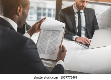Important agreement. Back view of young professional african man is reading document. He is sitting at table with his colleague who is typing on laptop. Selective focus