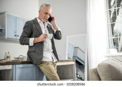 Important call. Cheerful man keeping smile on his face and holding telephone near left ear while looking downwards