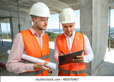Important details to discuss. Two engineers looking over paperwork together while at the construction site