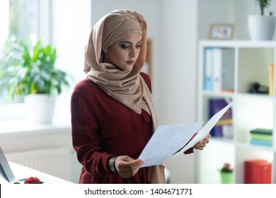 Important documents. Appealing woman wearing hijab reading important documents while working