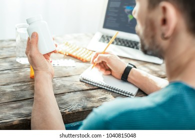 Important information. Concentrated serious focused man sitting in the bright room by the table holding a jar and writing.