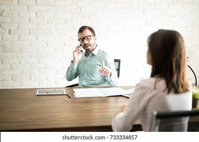 Important man making a client wait while he talks on the phone in his office