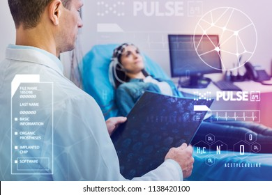 Important medical procedure. Calm attentive professional doctor thoughtfully looking at the results of electroencephalography while standing not far from his young patient