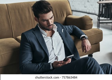 Important message. Handsome young man in full suit holding a smart phone and looking away while sitting on the floor at home