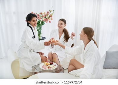 Important occasion. Smiling young ladies in white bathrobes holding alcohol drinks and toasting. Girls sitting on daybeds near table with sweets