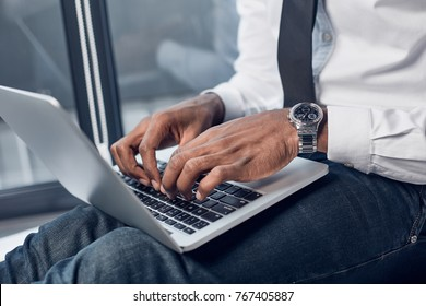 Important task. Close-up of hands of young african manager is sitting and holding laptop on his knees while typing on keyboard