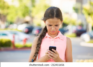 Important text message. Portrait teenage girl looking concerned with text message on her phone, isolated outdoor street background. Human face expressions, emotions, body language, reaction, feelings