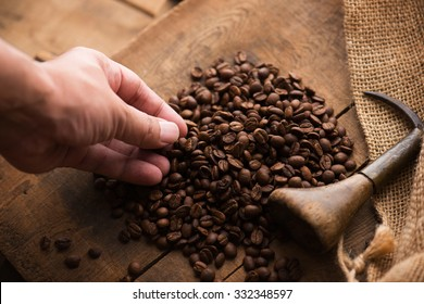 Imported coffee beans spilling out from a hemp sack, on wooden crate lid. Inspecting imported coffee beans. Focus is on the coffee beans. Shallow depth of field.