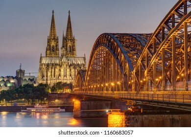 The imposing cathedral of Cologne with the Hohenzollern bridge over the river Rhine at dusk