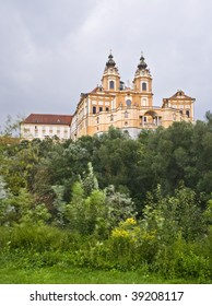 Imposing facade of the Abbey of Melk, located in Austria, over the trees of a forest next to the Danube river