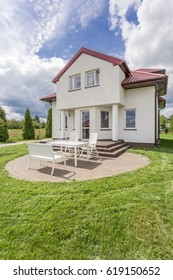 Imposing storey house with round porch with garden furniture