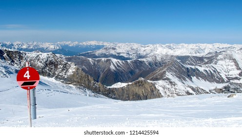 Imposing view of Hintertux Glacier ski slopes with rocky mountains, snow, clouds and a slope marker.