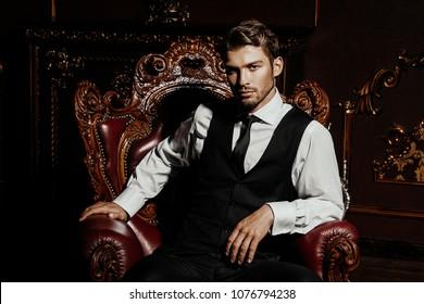 Imponente homem bem vestido sentado em uma poltrona em apartamentos luxuosos com interior clássico. Luxo. Beleza masculina, moda.
