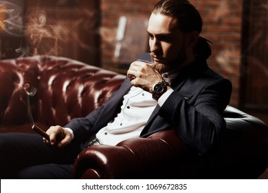 Imposing young man sitting on a leather sofa, drinks whiskey and smokes a cigar in a modern interior. Men's beauty, fashion.