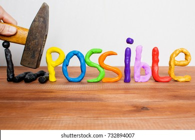 Impossible becomes possible, plasticine letters making word Impossible, two letters destroyed by a hammer.