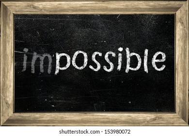 Impossible handwritten with white chalk on a blackboard.