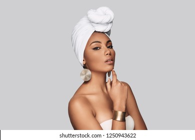 Impossible to resist her. Attractive young African woman in turban keeping hand on chin while standing against grey background