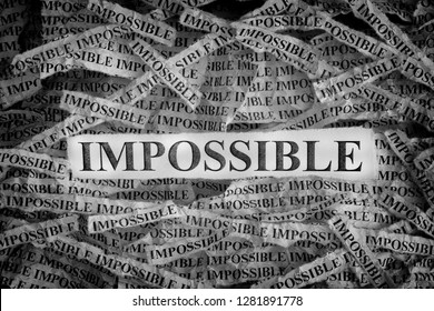 Impossible. Torn pieces of paper with the words Impossible. Concept image. Black and White. Close up.