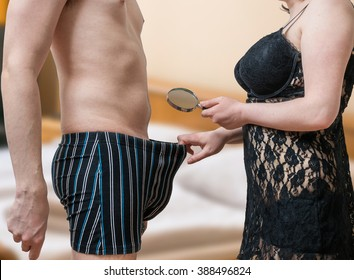 Impotence concept. Sexy woman is looking on her lovers penis with magnifying glass.