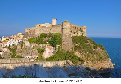 Impregnable castle of the Italian city of Gaeta in the rays of the setting sun on blue sky background and the sea