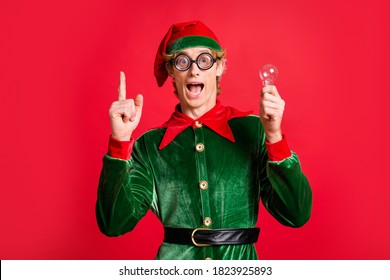 Impressed crazy elf raise finger hold light bulb creative think concept wear green costume isolated on red shine color background