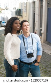 Impressed excited couple of tourists looking at landmark. Young man and woman with camera standing in old town street and looking away. Travel concept