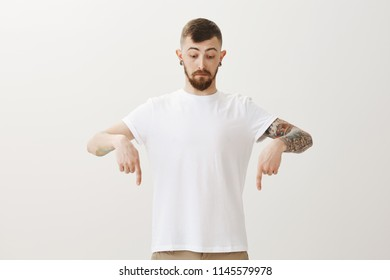 Impressed handsome bearded adult guy with tattoos, pointing and looking down with surprised and curious expression, seeing something impressing and interesting while standing over gray wall