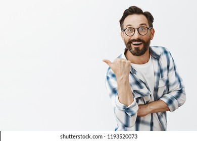 Impressed happy and excited good-looking male scientist in glasses, pointing backwards or left with thumb and gazing with thrilled expression at camera while describing amazing place he went to