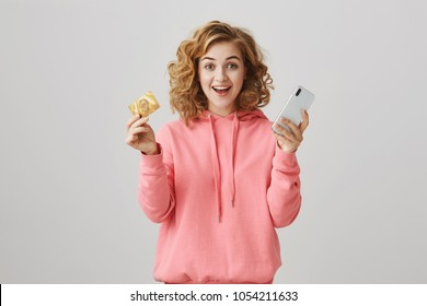 Impressed young good-looking european woman with curly hair holding credit card and cellphone, being happy and excited, standing over gray background. Bank offered good percent of cashback