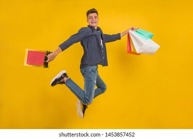 Impressed young man with colorful shopping bags in hands with open mouth, happy after successful shoping, isolated over yellow background