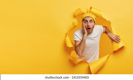 Impressed young man touches cheek, has stupefied facial expressions, drops jaw and stares at camera, looks out of hole in paper, cuts through yellow wall with empty space for your information