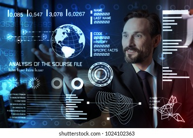 Impressing results. Clever experienced qualified programmer feeling impressed by the development of technologies and smiling while looking at the information on a transparent screen
