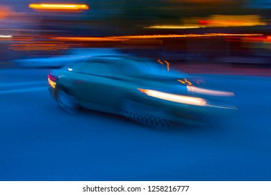 Impression of a car in motion speeding past bright city lights