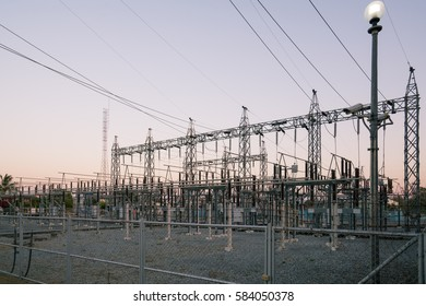 Impression network at transformer station in sunrise, high voltage up to twilight sky. High-voltage wires and transformer - Electrical distribution station.