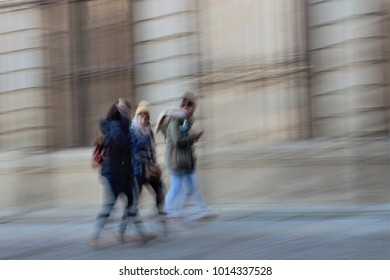 Impressionist photography of people taken at low speed, blurred movement,person walking on the street during the day, blurred background, movement sensation,ghostly shadows, in toledo, spain,