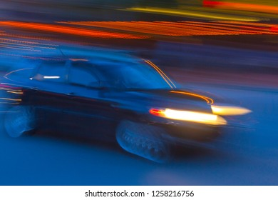 Impressionistic long exposure of a car speeding past city lights