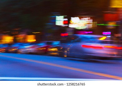 Impressionistic long exposure of a car speeding down a city street alongside parked cars and lit up businesses