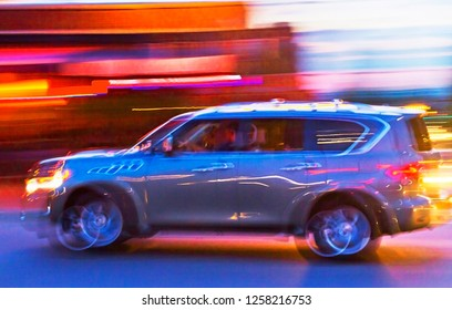 Impressionistic long exposure shot of a car full of young people speeding through the light of a city at twilight