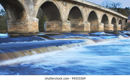 Impressive ancient Bridge found in Hexham, England over stunning Blue atmospheric soft Waterfall