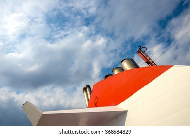 Impressive boat's chimney showwing off among the cloudy sky.